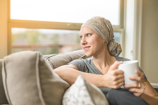 ethnische junge erwachsene krebspatientin schlürft tee - chemotherapie stock-fotos und bilder