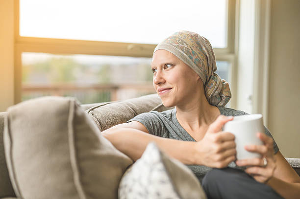 ethnic young adult female cancer patient sipping tea - cytostatica stockfoto's en -beelden
