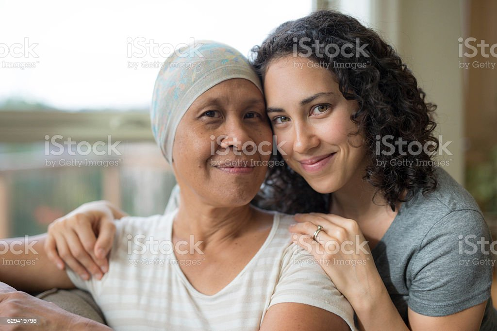 Ethnic young adult female hugging her mother who has cancer - foto de stock