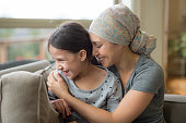 Ethnic young mom with cancer holding 8-year old daughter on couch