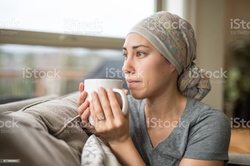 Ethnic young woman with cancer drinking cup of tea on couch stock photo