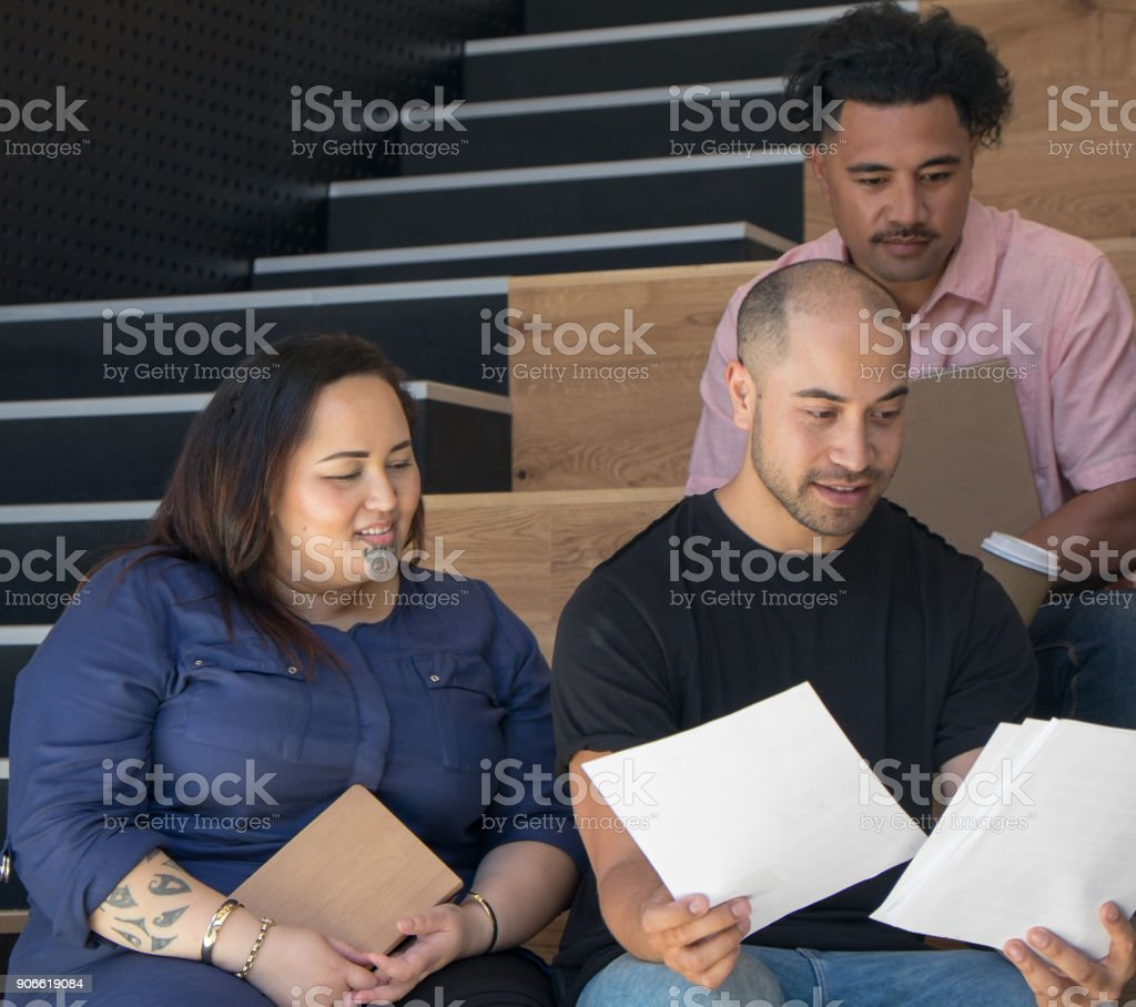 Ethnically diverse group of employees in business work place having a team meeting reviewing a document. stock photo