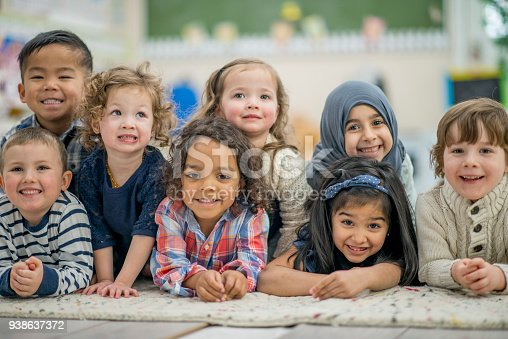 A group of eights adorable preschool children lay on the classroom carpet and smile