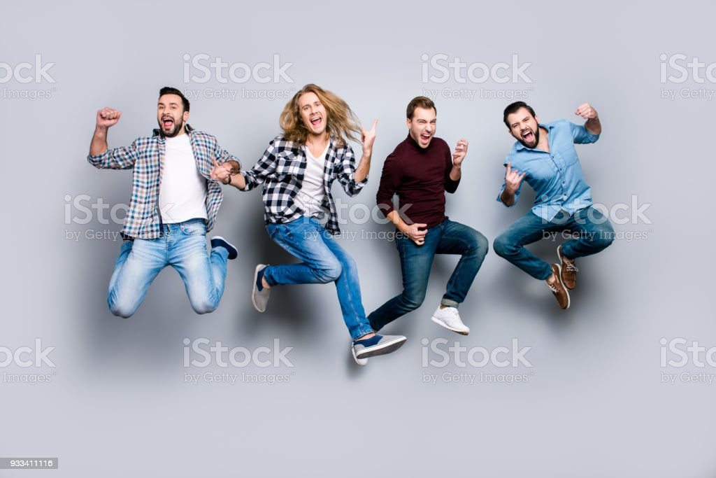 Ethnicity diversity careless freedom people chill hang-out figure playful funny showing symbols concept. Four excited cheerful active carefree men jumping up isolated on gray background royalty-free stock photo