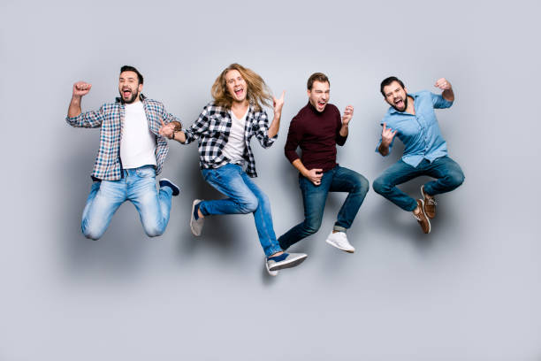 ethnicity diversity careless freedom people chill hang-out figure playful funny showing symbols concept. four excited cheerful active carefree men jumping up isolated on gray background - soccer supporter portrait imagens e fotografias de stock