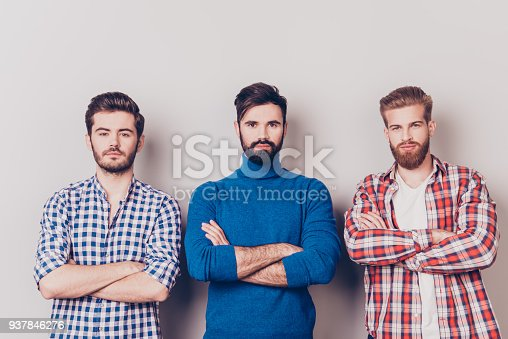 istock Ethnicity, multicultural diversity. Three serious harsh men are standing isolated on pure background with crossed hands, dressed in casual clothes 937846276