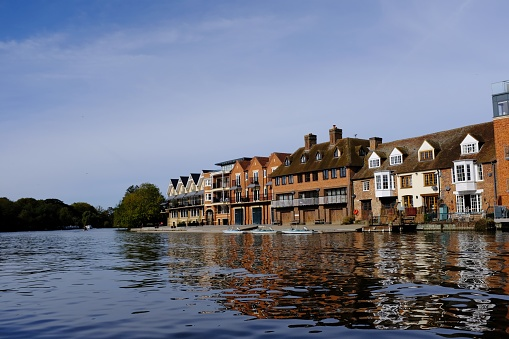 istock Eton seen from Windsor across the River Thames, England, with boathouses and other buildings reflected in the water on an autumn morning 1054724500