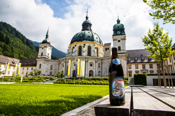 Ettal Abbey, Germany A bottle of Ettaler beer in front of the main facade of of Ettal Abbey (Kloster Ettal), a Benedictine monastery in the village of Ettal, Bavaria, Germany abbey monastery stock pictures, royalty-free photos & images