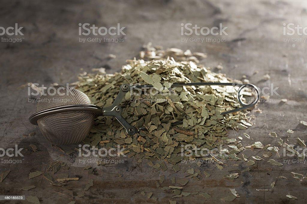 Eucalyptus Tea and tea-strainer on a metal texture stock photo