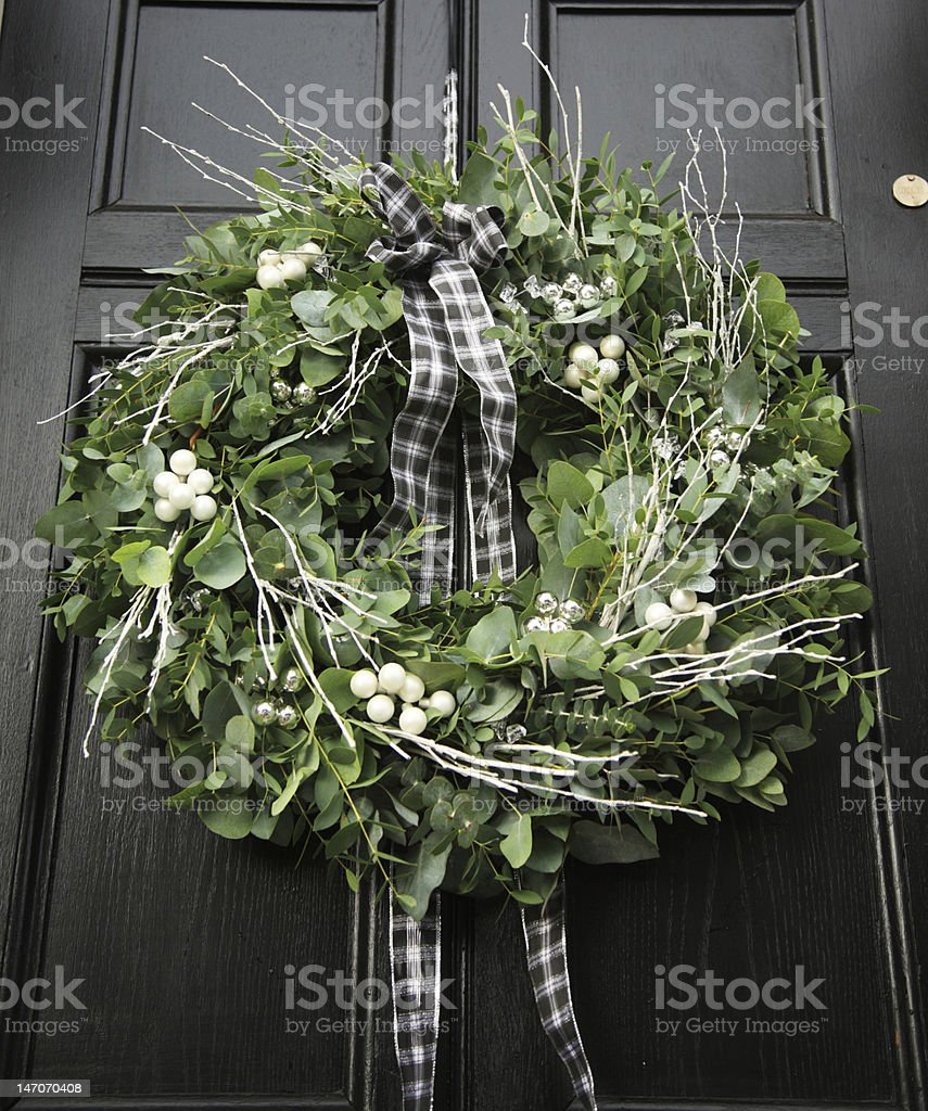 Eucalyptus wreath - modern Christmas wreath hung on a black door royalty-free stock photo