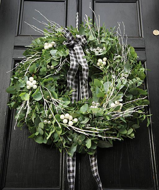eukalyptus-kranz-moderne weihnachten kranz auf einem schwarzen tür hing - türbänder stock-fotos und bilder