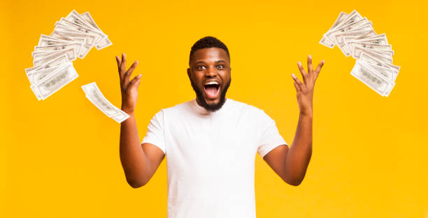 euphoric black man throws up lots of dollars - throw money away stock pictures, royalty-free photos & images