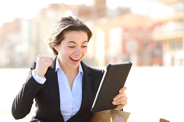 Euphoric successful executive watching a tablet stock photo