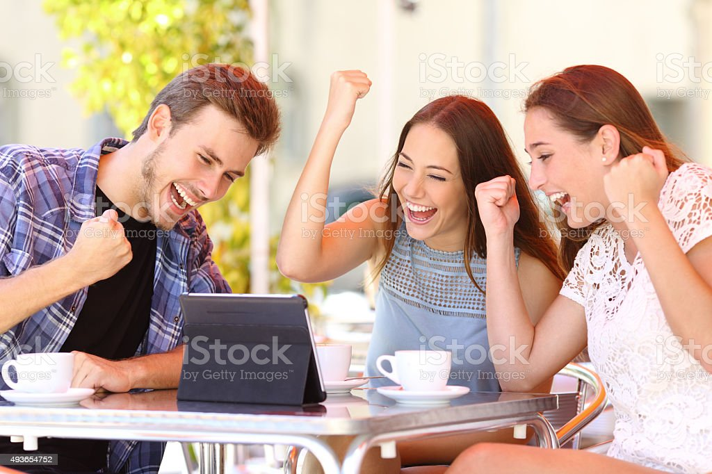 Euphoric winner friends using a with a tablet stock photo