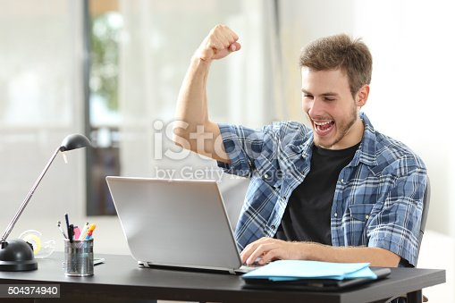 493712130 istock photo Euphoric winner man using a laptop at home 504374940