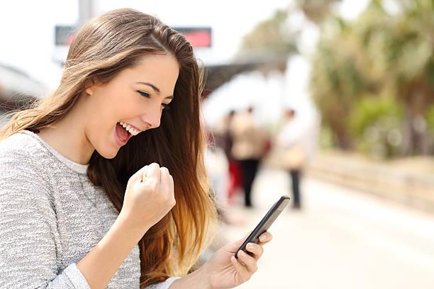 vitalisierendes frau vor ihrem smartphone in einen bahnhof - die besten apps stock-fotos und bilder