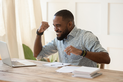 istock Euphoric young black man celebrating online lottery win. 1177334862