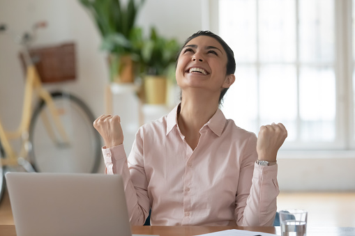 Euphoric young indian businesswoman making yes gesture, feeling excited about professional achievement. Happy hindu woman celebrating success, online lottery win, receive good news at workplace.