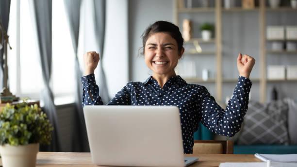歡欣鼓舞的年輕印度女孩慶祝線上勝利與筆記本電腦 - 成功 個照片及圖片檔