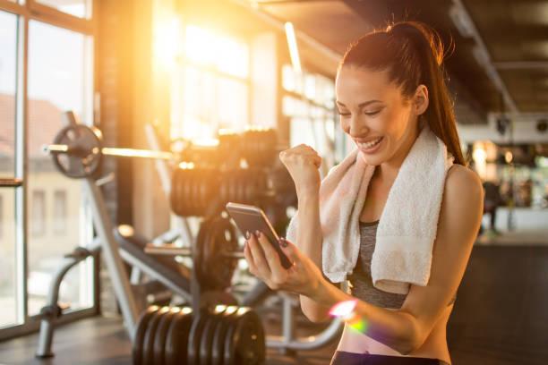 euphorische junge frau mit schönen lächeln gute nachrichten auf dem handy lesen und erfolge zu feiern, während pause training im fitness-studio - die besten apps stock-fotos und bilder