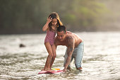Ethnic dad with tattoos all along his left arm helps teach his young daughter how to surf. They are in shallow water and he is steadying the board while she stands on it. She has an excited expression on her face.
