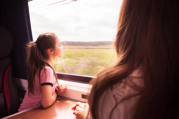 Eurasian girl and Mother enjoying traveling by train in Yorkshire, UK stock photo