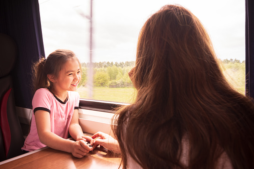 Pretty 8 year old Eurasian (mixed race) girl is enjoying taking the train from Edinburgh to York, and is somewhere in the middle of rural Yorkshire. She's enjoying the view out of her window set. She's traveling with her mother.