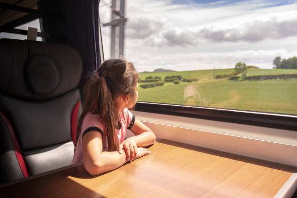Eurasian girl enjoying traveling by train in Yorkshire, UK stock photo