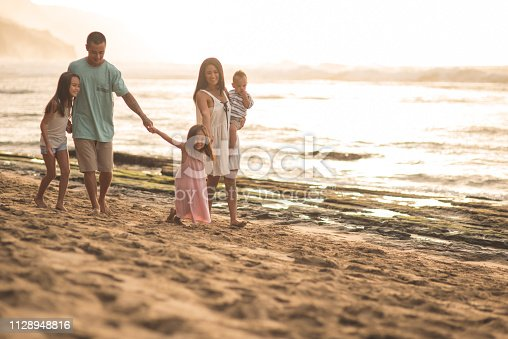 Mom and dad walk with their three young children along a sandy Hawaiian beach. They are wearing swimwear and holding hands. The waves are washing up on shore on the right side of frame.