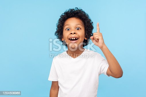 Eureka! Portrait of smart little boy with curly hair pointing finger up and looking inspired by genius thought, showing good idea sign, having clever solution in mind. studio shot blue background