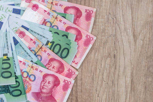 100 euro and 100 yaun bills on desk. 100 euro and 100 yaun bills on desk. chinese currency stock pictures, royalty-free photos & images