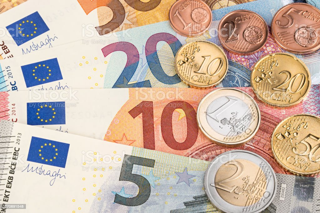 euro and cent coins on bank notes – Foto