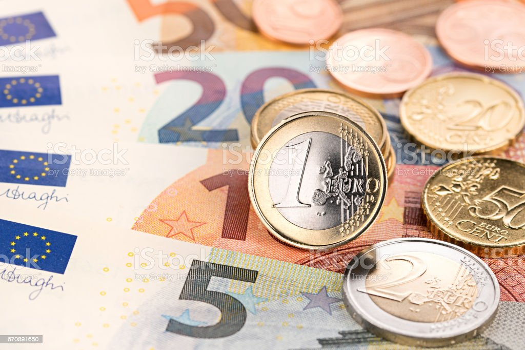 euro and cent coins on bank notes stock photo