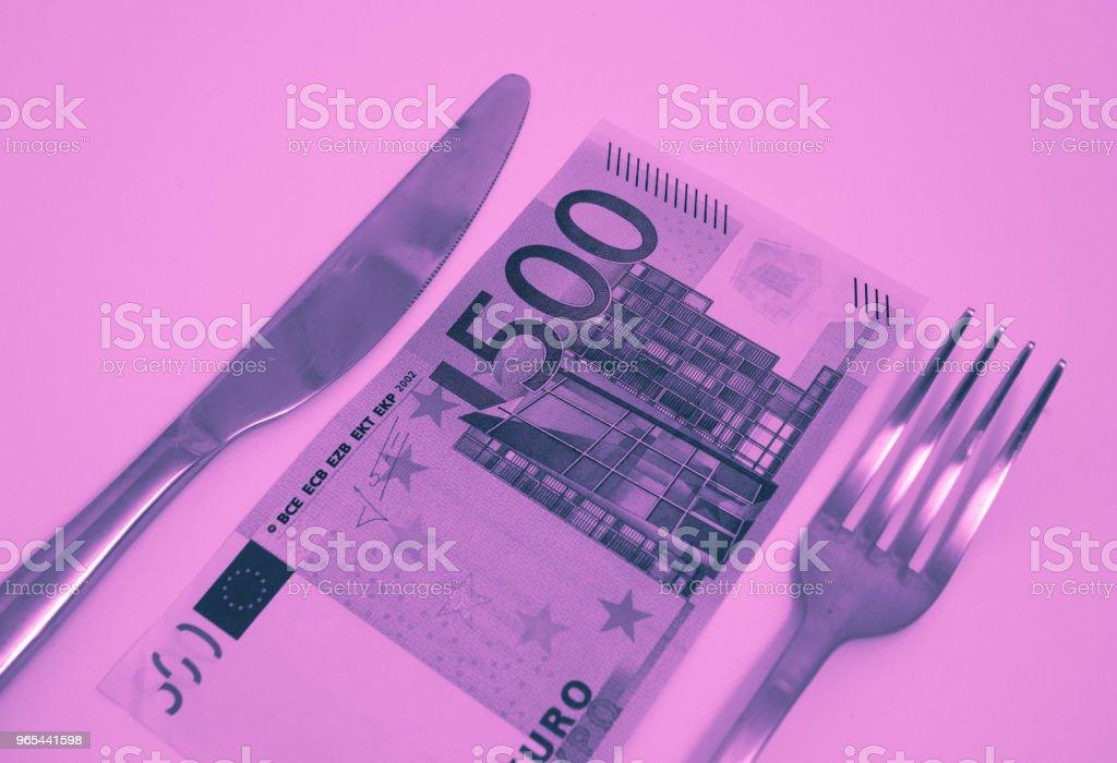 Uma nota de 500 euros, deitado em uma mesa com garfo e faca. Conceito de comida de restaurante caro. - Foto de stock de Almoço royalty-free