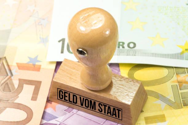 Euro Geldscheine und ein Stempel mit dem Aufdruck Geld vom Staat – Foto