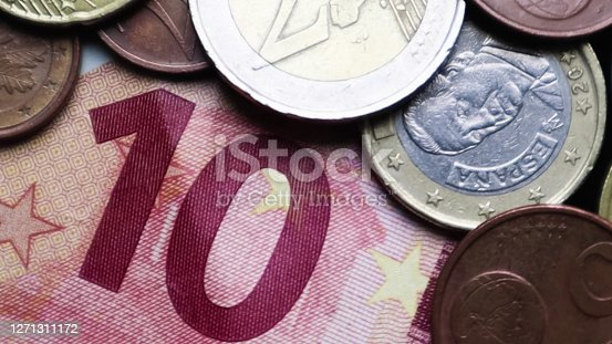 Euro banknotes and coins as background. Shot looking at the Euro currency. Coins are stacked on top of each other in different positions. Money concept