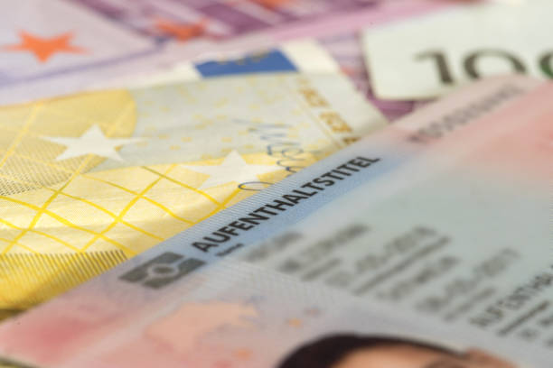 Euro banknotes and residence permit for Germany stock photo