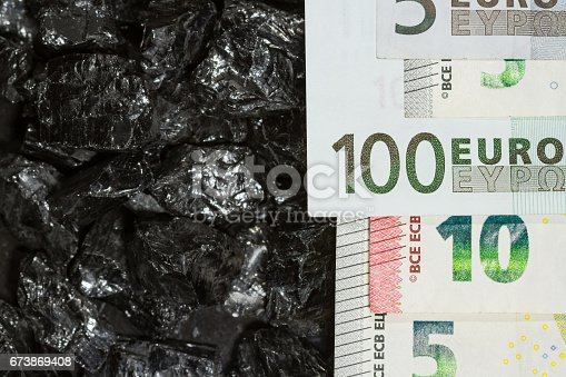 istock Euro banknotes on raw coal nuggets, bills on coal, power of money and ore 673869408