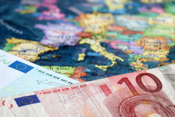 euro banknotes on the map of europe, selective focus. concept for european economy, eurozone countries - cartina italia foto e immagini stock