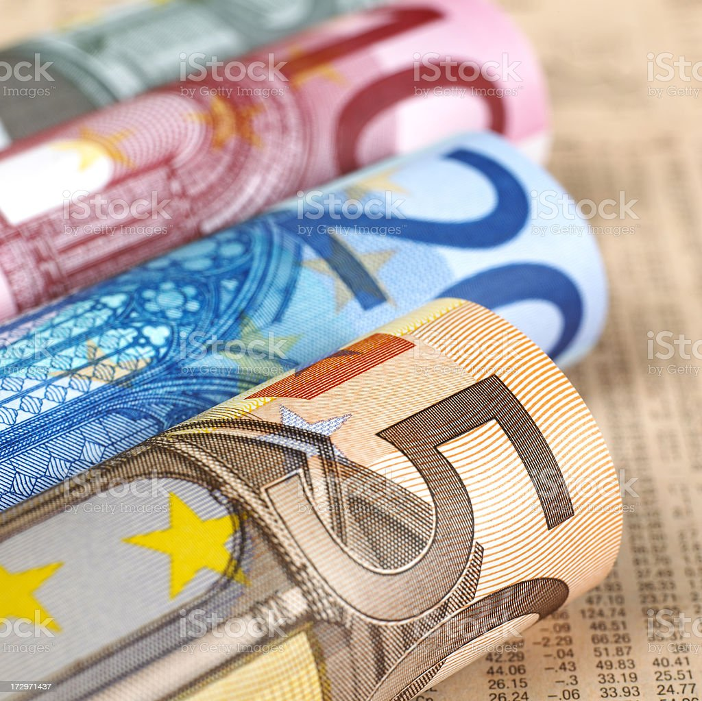 Euro banknotes rolled up on financial newspaper stock photo