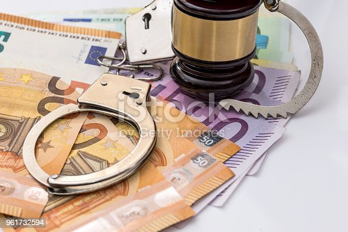 1024130248istockphoto Euro banknotes with handcuffs and gavel on white background 961732594