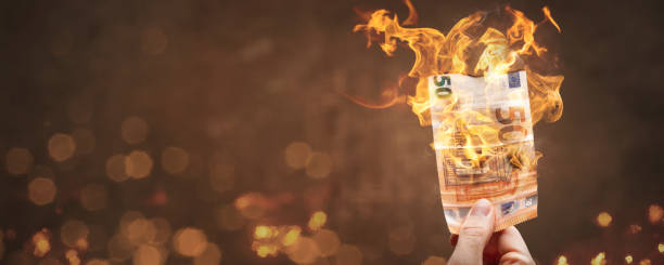 50 Euro bill burning with a bright flame A hand-held 50 Euro banknote is burning with a bright flame. With copy space to the left. depreciation stock pictures, royalty-free photos & images