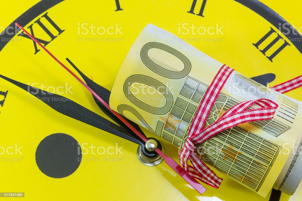 Euro bills on top of the clock stock photo