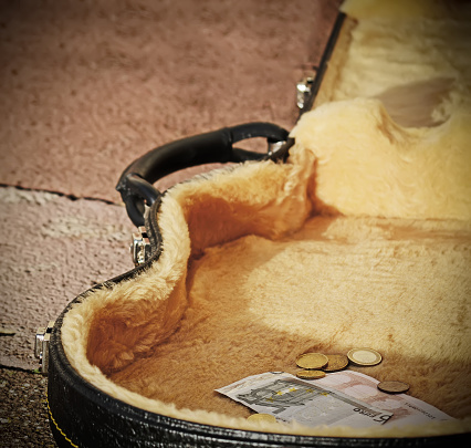 istock euro coins and bills in a guitar case 537452563