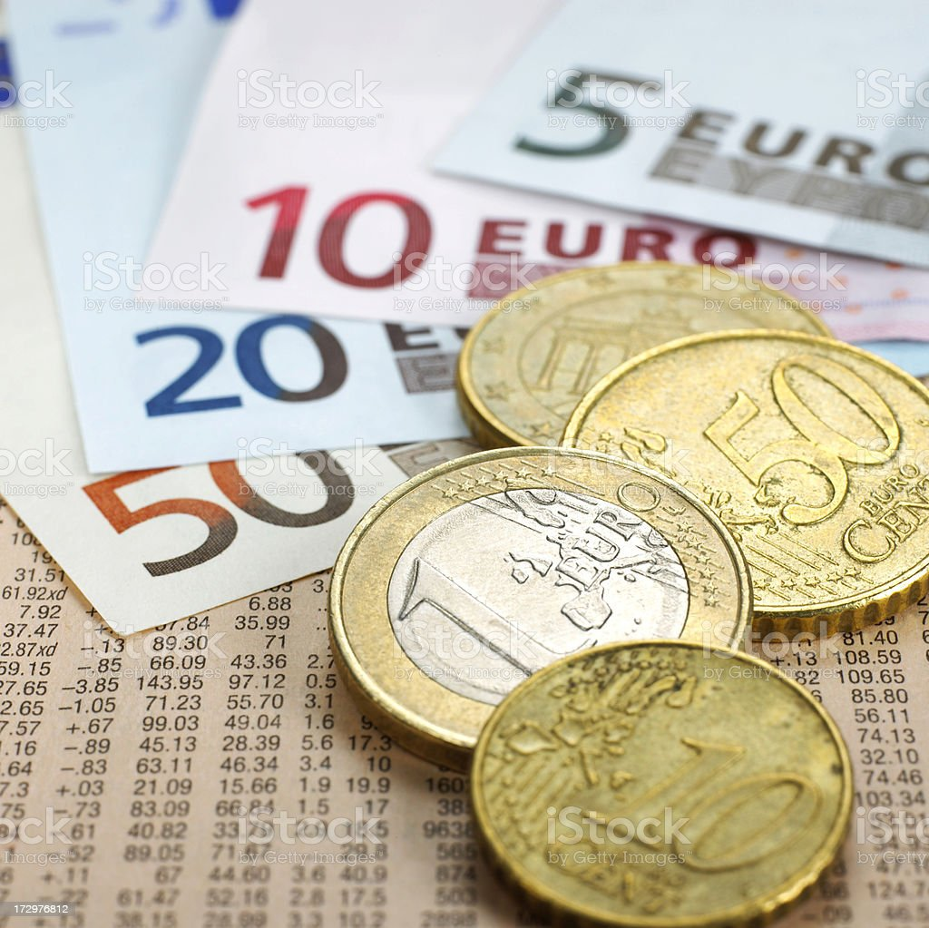 Euro coins and notes on financial newspaper stock photo