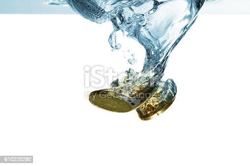 istock Euro coins falling in water with splash, isolated on white 610225292