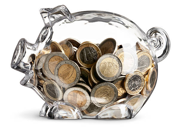 Euro Coins In Nearly Full Clear Savings Piggy Bank Concept of a clear isolated piggy bank nearly filled of Euro coins - clipping path provided Canon 5D MarkII european union coin stock pictures, royalty-free photos & images