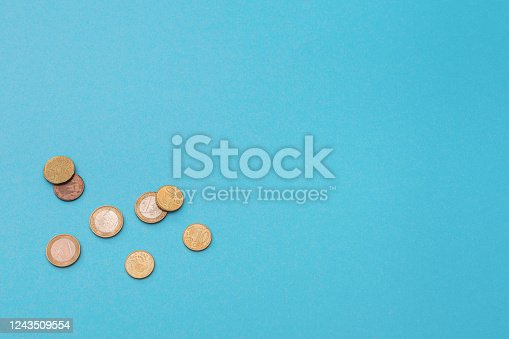 istock Euro coins on a blue background 1243509554