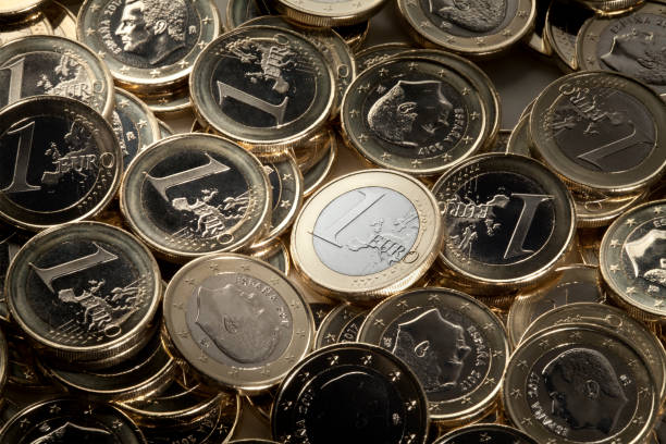 Euro coins One euro coin prominent from among many euro pieces. euro symbol stock pictures, royalty-free photos & images