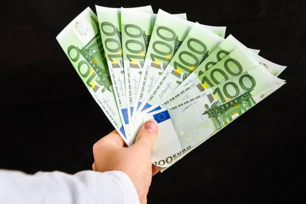 euro currency, european uninon money, hand holding euros cash on the black background stock photo